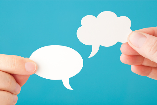 Hands Hold Two Blank Speech Bubbles Stock Photo - Download Image Now