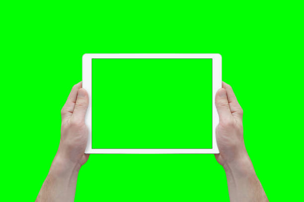 hands hold white tablet in a horizontal position. view from first person. isolated screen and background in green. - green screen background stock photos and pictures
