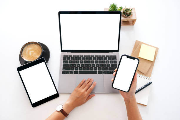 Zeiger halten ein leeres weißes Bildschirm-Handy mit Laptop-Computer und Tablet-PC auf dem Tisch im Büro – Foto