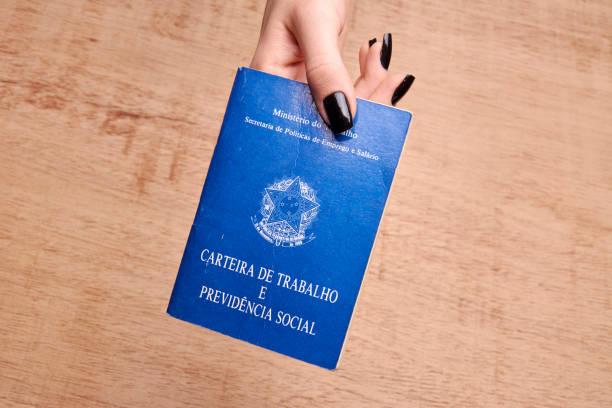 hände halten ein brasilianischer sozialversicherung dokument. - wirtschaftsrecht stock-fotos und bilder