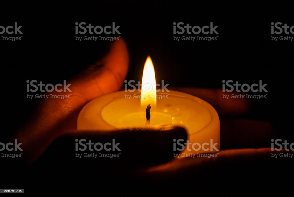 Hands holding a candle stock photo