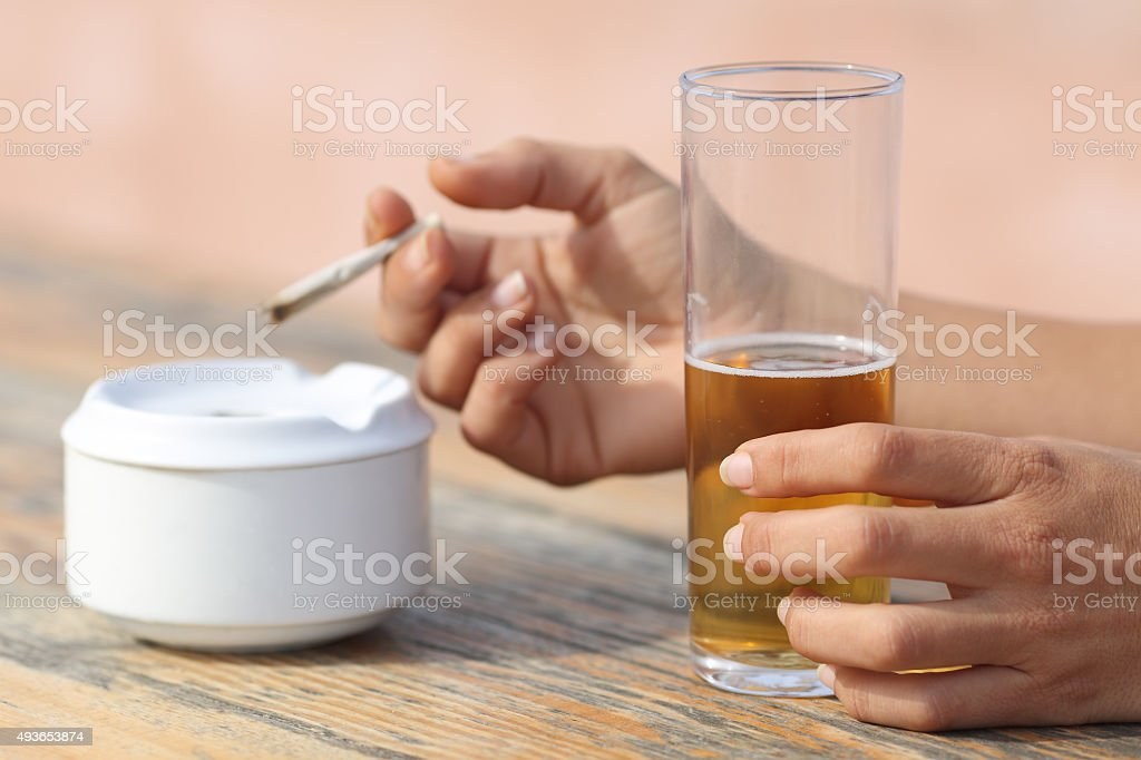 Hands holding a cigarette smoking and drinking alcohol Woman hands holding a cigarette smoking and drinking alcohol in a bar table 2015 Stock Photo