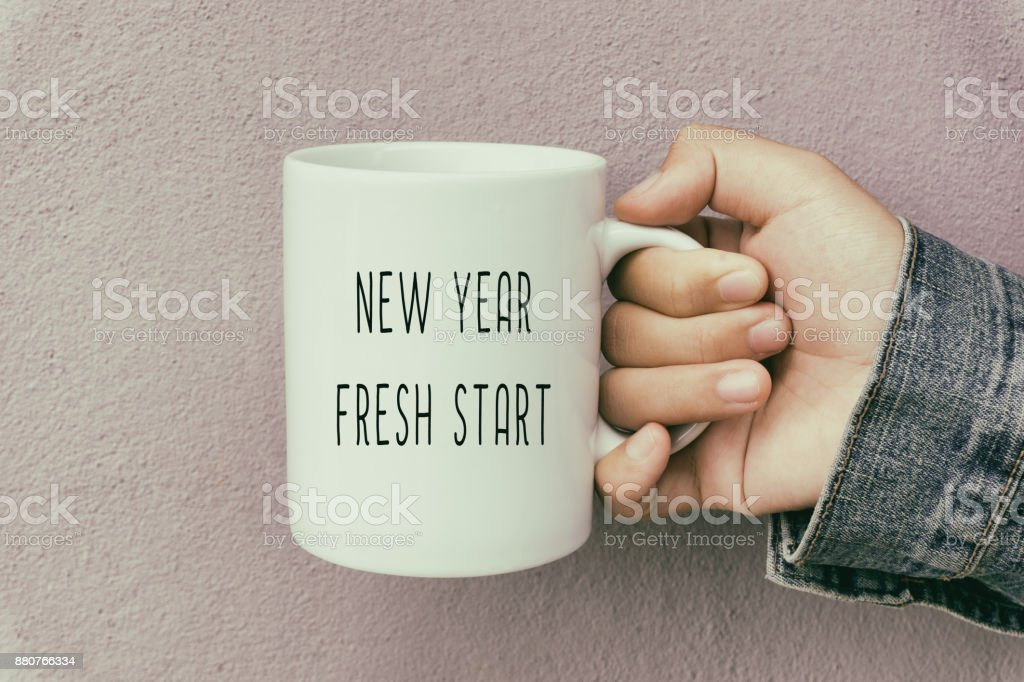 Hands Holding a Coffee Mug With Text New Year Fresh Start stock photo