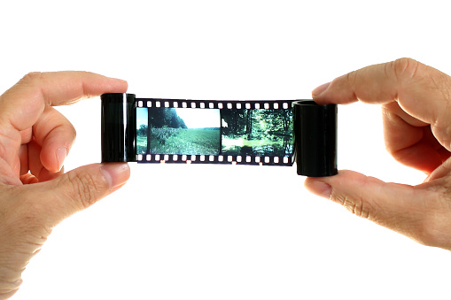 Hands holding a film on a white background