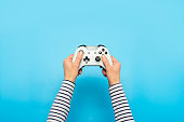 istock Hands holding a gamepad on a blue background. Banner. Concept games, video games 1252386803