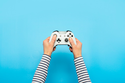 Hands holding a gamepad on a blue background. Banner. Concept games, video games