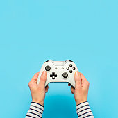 istock Hands holding a gamepad on a blue background. Banner. Concept games, video games 1269271483