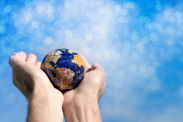 Hands Holding a Globe Towards Sky stock photo