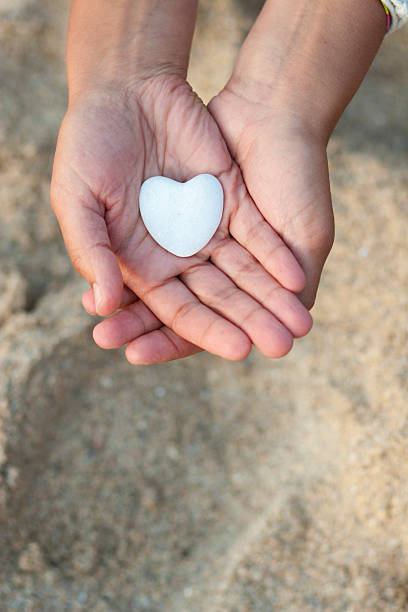 Hands holding a heart on defocused sand background. stock photo