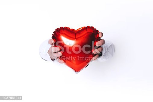 1078237178 istock photo Hands holding a heart on white background. Creative minimal concept. 1087561244