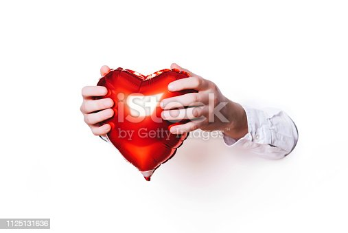 1078237178 istock photo Hands holding a heart on white background. Creative minimal concept. 1125131636