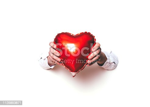 1078237178 istock photo Hands holding a heart on white background. Creative minimal concept. 1125853871