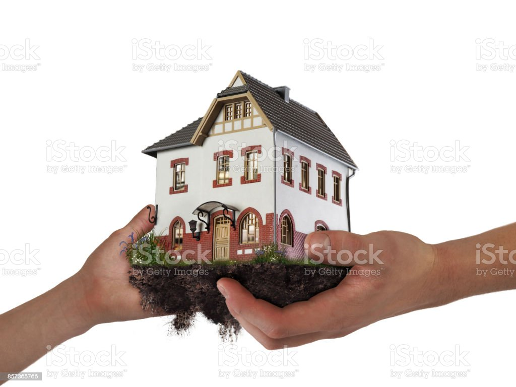 Hands holding a house. The concept of relocation, mortgage, inheritance, stock photo