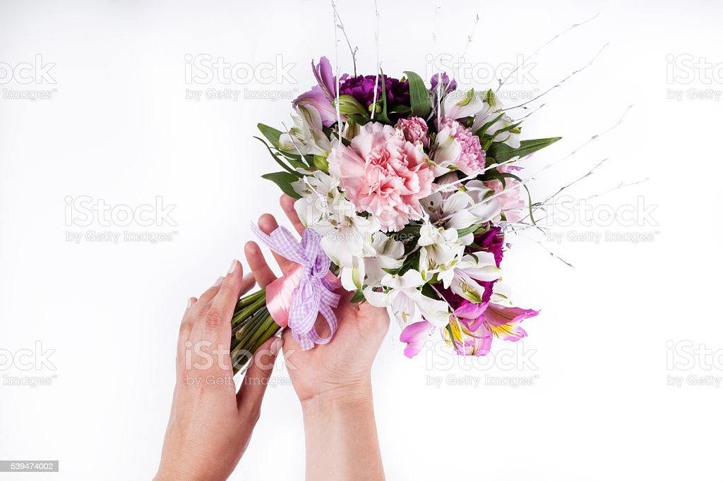 Hands holding a pastel bouquet from pink and purple gillyflowers stock photo