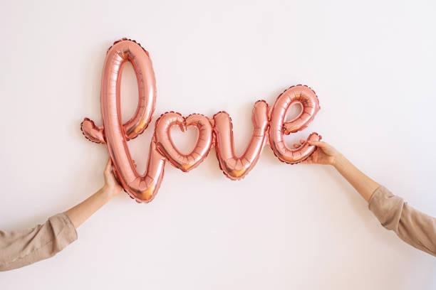 Hände halten einen rosa Folie Ballon - Wort LIEBE – Foto
