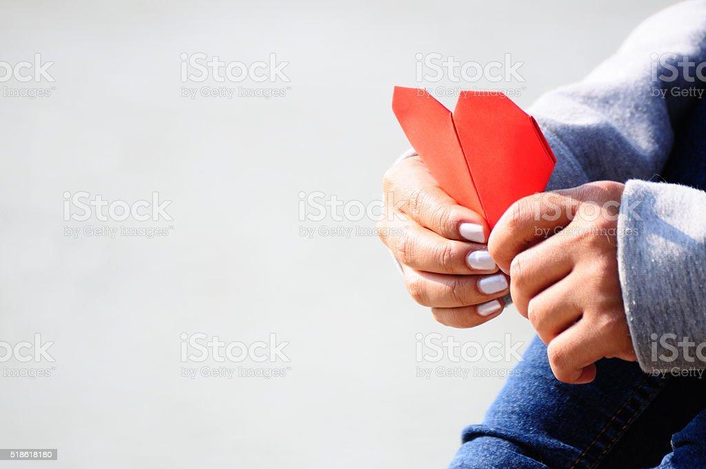 Hands Holding a Red Heart Shape Paper bildbanksfoto