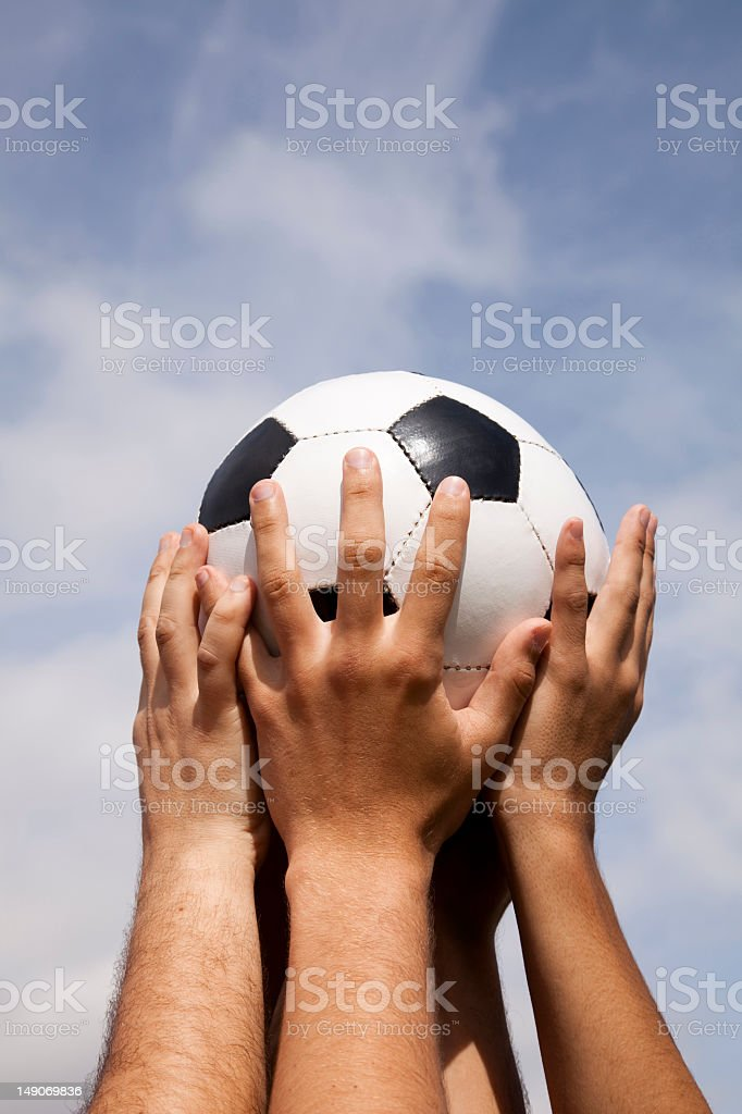 Hands holding a soccer ball in the air royalty-free stock photo