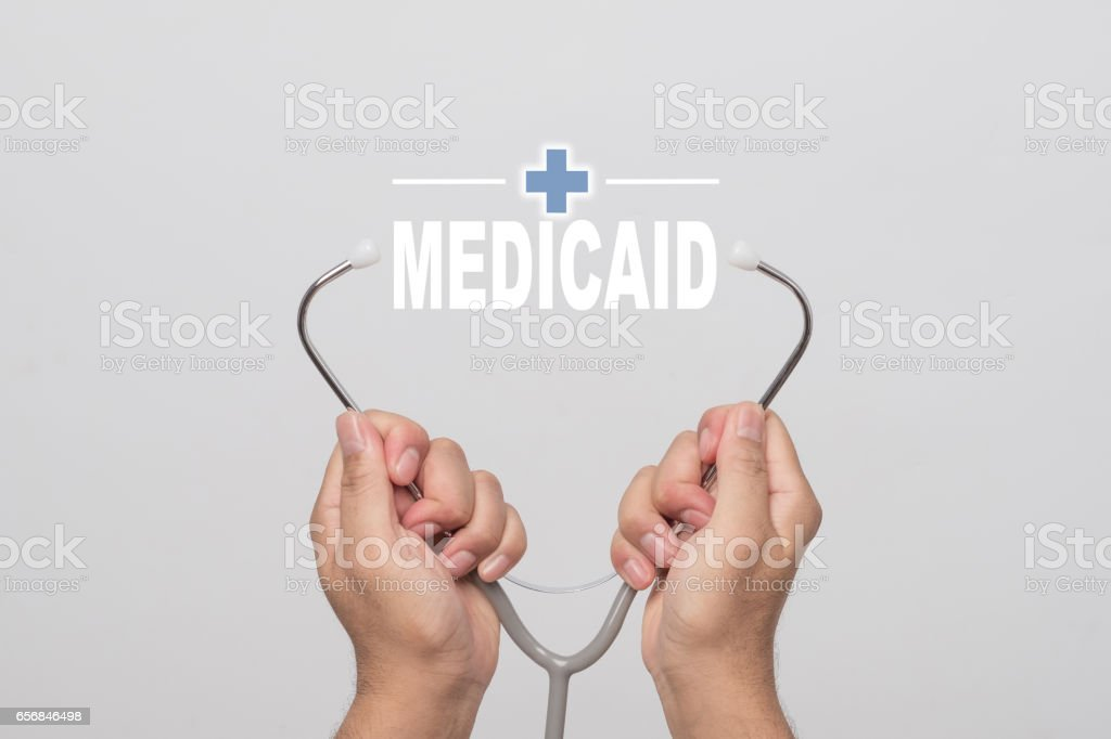 Hands holding a stethoscope and word 'MEDICAID'  medical concept. stock photo