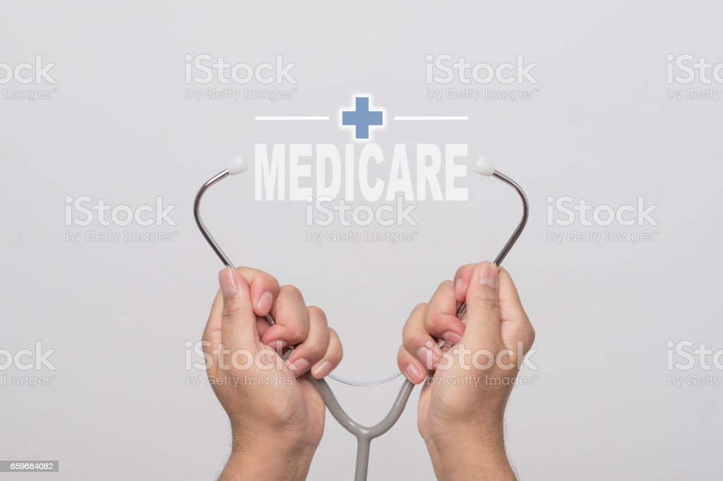 Hands holding a stethoscope and word  'MEDICARE' on gray background. concept Healthy. stock photo