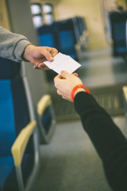 hands holding a white ticket - transport conductor stock photos and pictures
