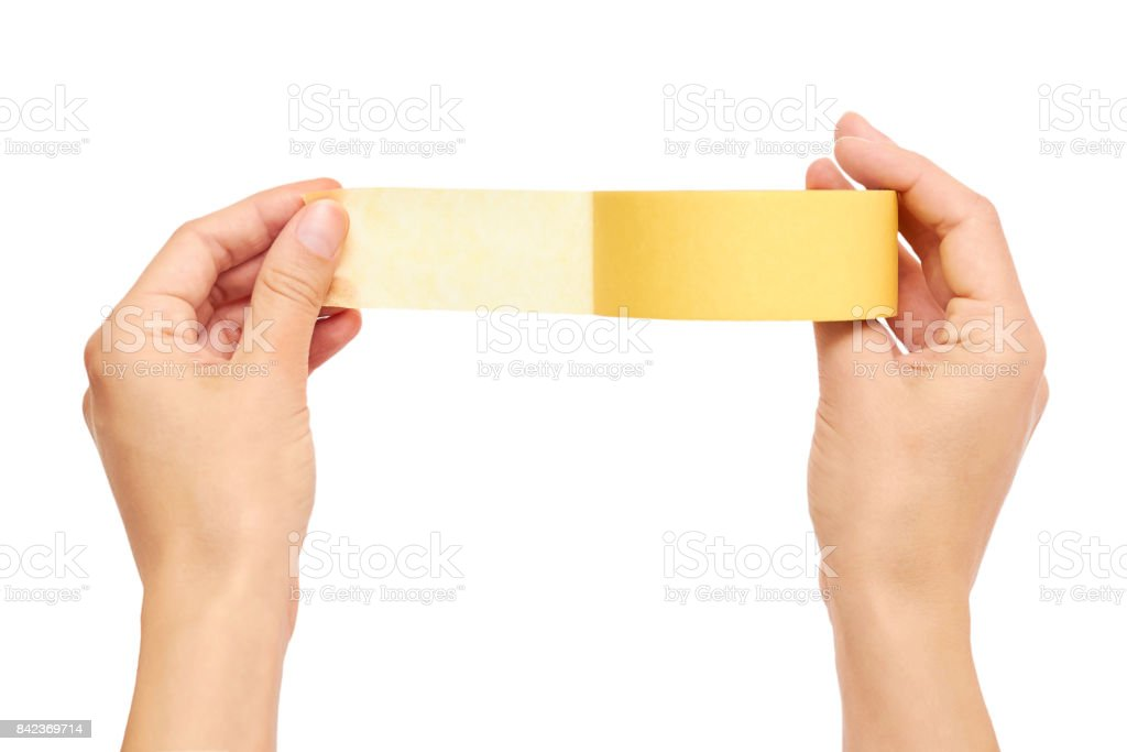 Hands holding a yellow adhesive tape isolated on white background stock photo