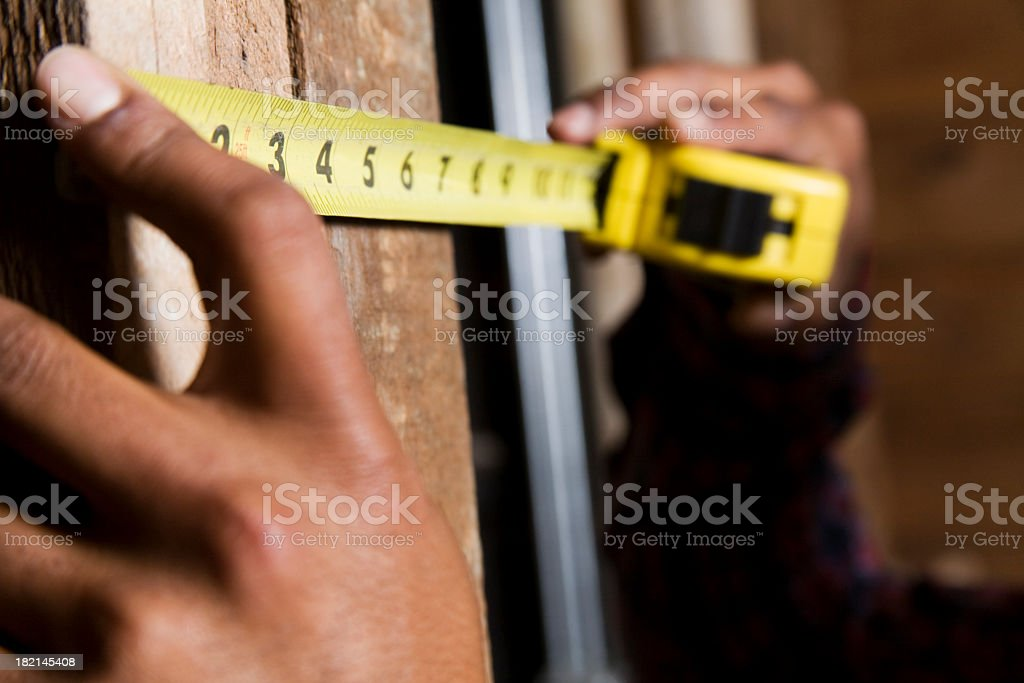 Hands holding a yellow measuring tape against a wooden wall royalty-free stock photo