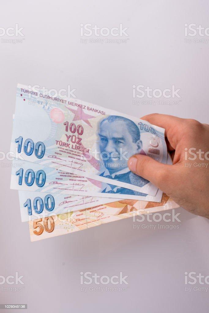 Mãos segurando ilhas Lira notas e notas de dólar americano ao lado - foto de acervo