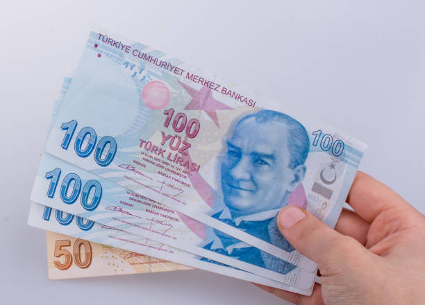 Hands holding American dollar banknotes and Turksh Lira banknotes side by side stock photo