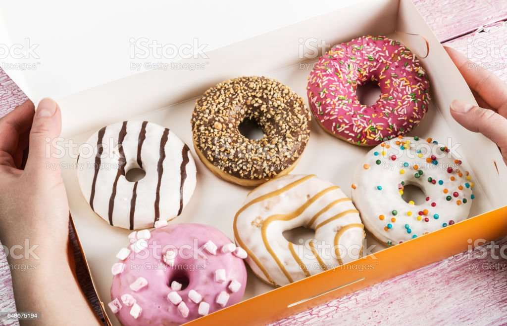 hands holding an open box of donuts stock photo