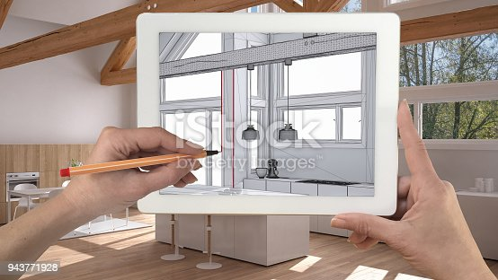 894638730 istock photo Hands holding and drawing on tablet showing modern kitchen sketch. Real finished minimalist white and wooden kitchen in the background, architecture interior design presentation 943771928