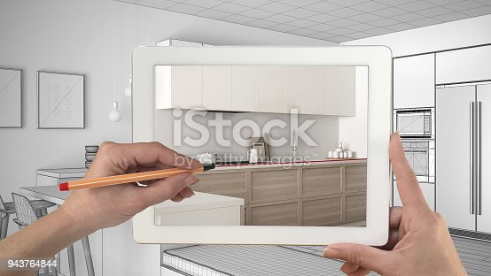 894638730 istock photo Hands holding and drawing on tablet showing real finished minimalist white and wooden kitchen. Modern kitchen sketch in the background, architecture interior design presentation 943764844