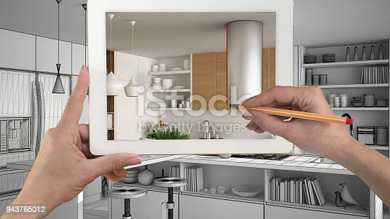 894638730 istock photo Hands holding and drawing on tablet showing real finished minimalist white and wooden kitchen. Modern kitchen sketch in the background, architecture interior design presentation 943765012