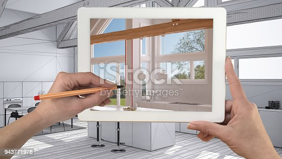 894638730 istock photo Hands holding and drawing on tablet showing real finished minimalist white and wooden kitchen. Modern kitchen sketch in the background, architecture interior design presentation 943771978