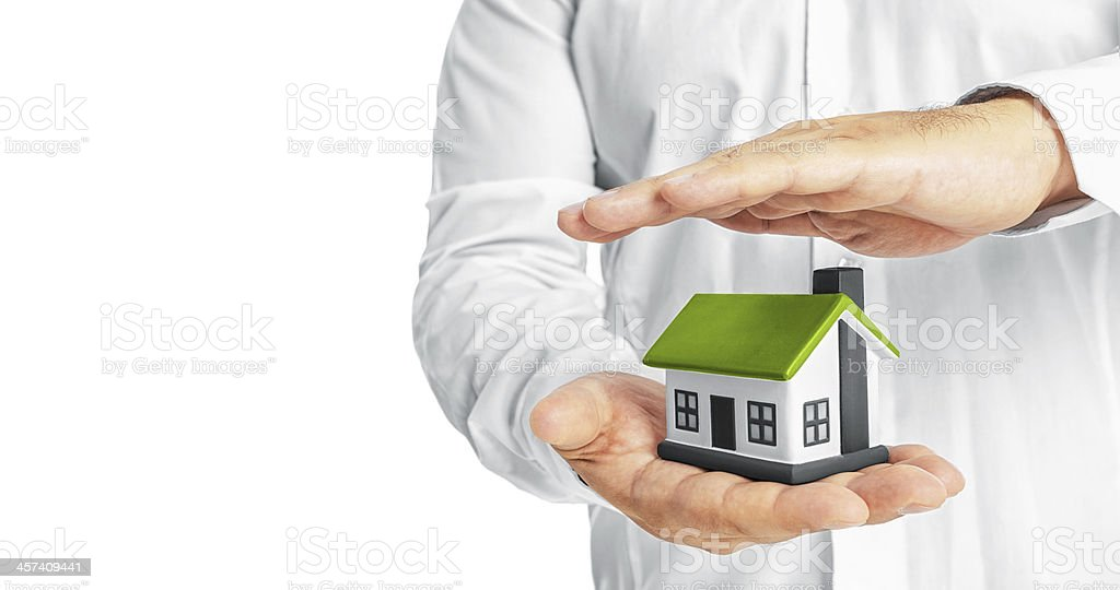 Hands holding and protecting a model house stock photo