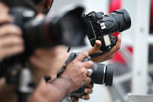 Manos sosteniendo y tomas de cámara slr - foto de stock