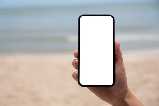 hands holding and showing a black mobile phone with blank desktop screen by the sea - phone, travelling, copy space imagens e fotografias de stock