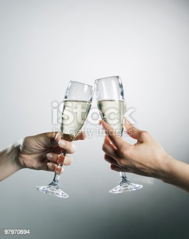 istock Hands holding and toasting champagne flutes 97970694