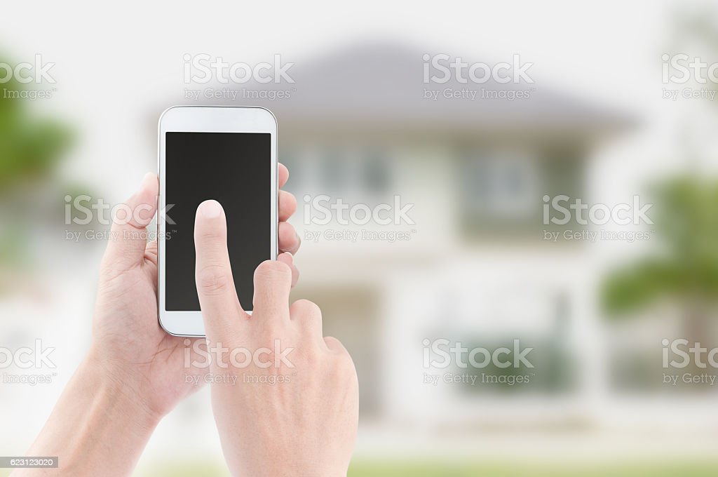 Hands holding and touch screen of smart phone on house - Photo