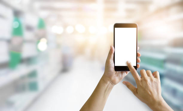 hands holding and using mobile smart phone in supermarket shop, shopping online concept - online shopping imagens e fotografias de stock