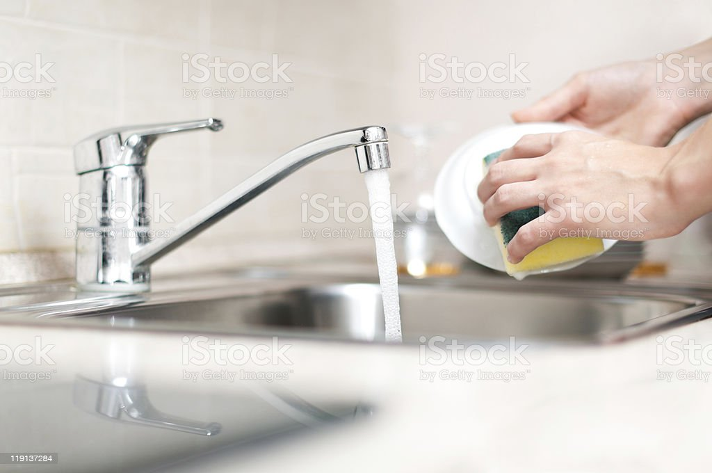 Hands holding and washing a bowl in the kitchen sink stock photo