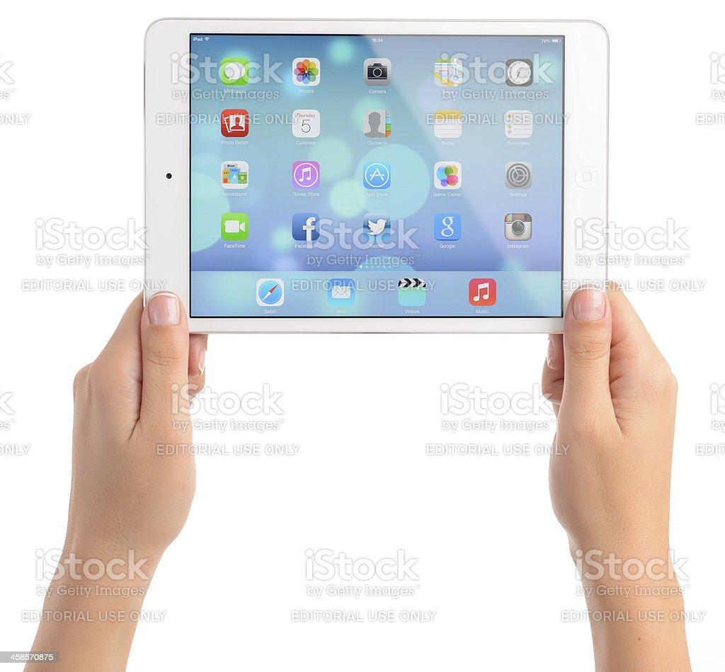 Hands holding Apple iPad Mini displaying iOS 7 home screen royalty-free stock photo