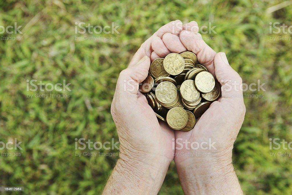 Hands holding Australian dollar coins over grass stock photo
