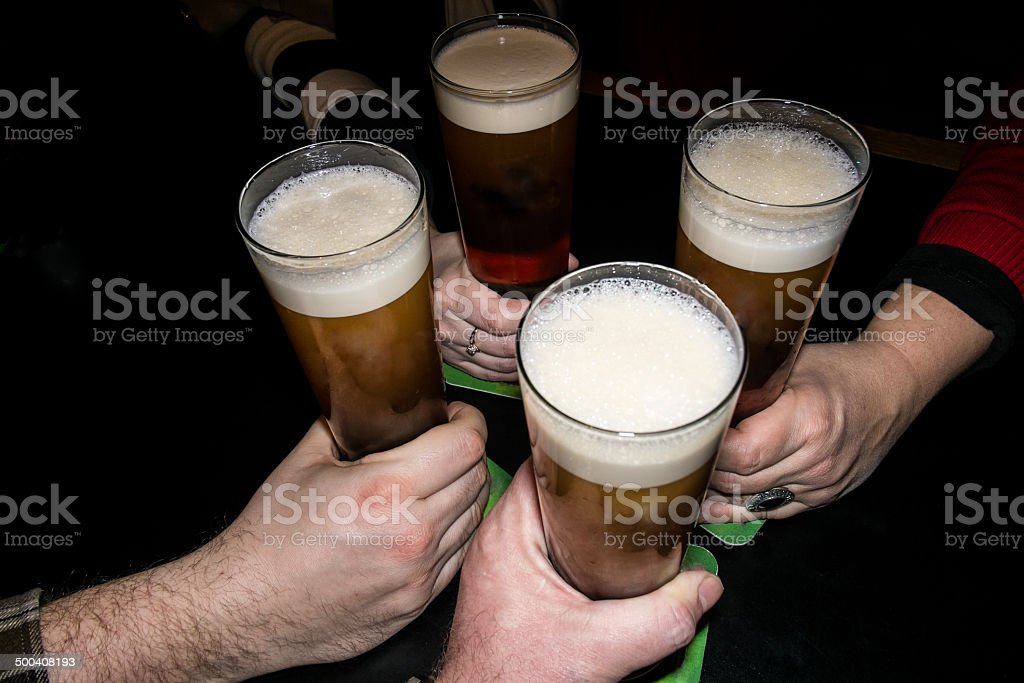 Hands holding beer drinking together in the pub stock photo