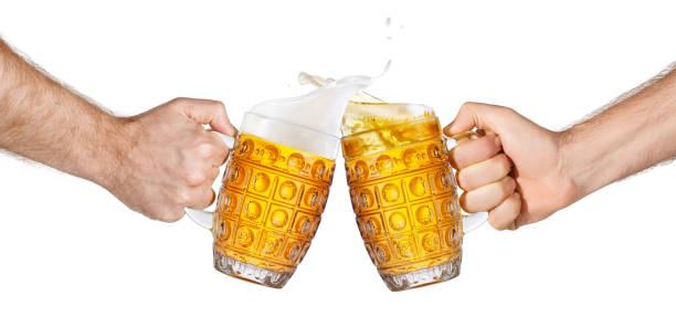 manos con jarras de cerveza haciendo tostadas - foto de stock
