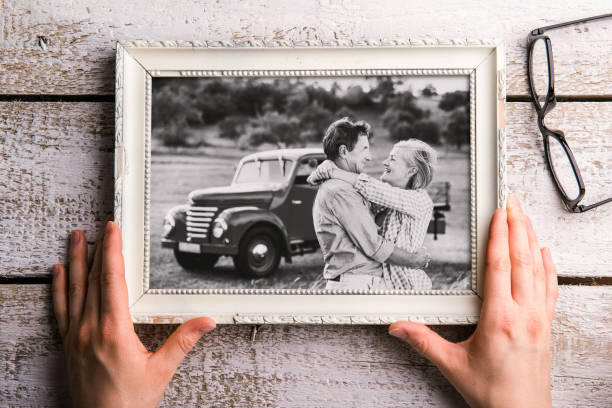 hands holding black-and-white photo of seniors in picture frame - schöne bilderrahmen stock-fotos und bilder