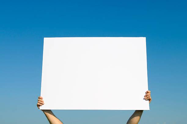 Mãos segurando Blank Billboard contra o azul Sky.Add sua mensagem - foto de acervo