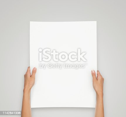 istock Hands holding blank paper sheet 1142841338