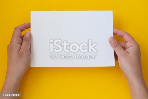 1159989540 istock photo Hands holding blank white, empty paper isolated on yellow with copy space 1149038339