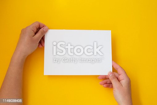 1159989540 istock photo Hands holding blank white, empty paper isolated on yellow with copy space 1149038405