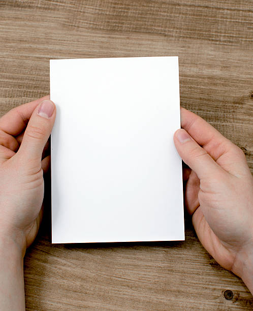 Hands holding blank white paper against wood background stock photo